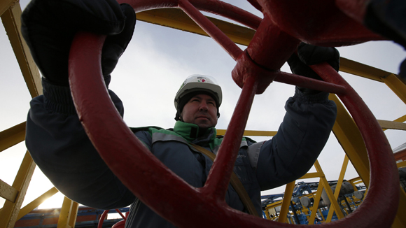 A worker adjusts the valve of an oil pipe at an oil reception and delivery point owned by Bashneft company near Kaltasy